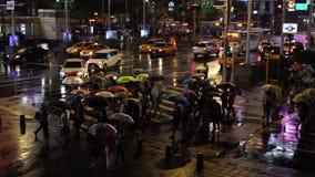 Calle que cruza de la gente delante del distrito de las compras de Ximending con lluvia el caer en la noche en Taipei, Taiwán almacen de metraje de vídeo