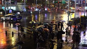 Calle que cruza de la gente delante del distrito de las compras de Ximending con lluvia el caer en la noche en Taipei, Taiwán almacen de video