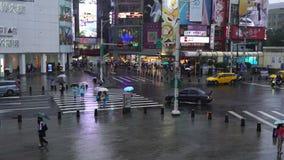 Calle que cruza de la gente delante del distrito de las compras de Ximending con lluvia el caer en Taipei, Taiwán almacen de metraje de vídeo