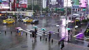 Calle que cruza de la gente delante del distrito de las compras de Ximending con lluvia el caer en Taipei, Taiwán almacen de video
