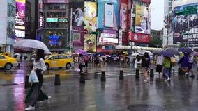 Calle que cruza de la gente delante del distrito de las compras de Ximending con lluvia el caer en Taipei, Taiwán metrajes