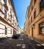 Calle vacía estrecha con los coches parqueados en Kraków, Polonia Imágenes de archivo libres de regalías