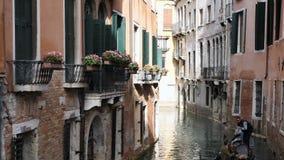 Calle veneciana clásica del canal o del canal con la góndola del montar a caballo almacen de metraje de vídeo