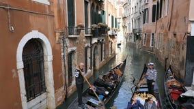 Calle veneciana clásica del canal o del canal con las góndolas del montar a caballo almacen de video