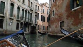 Calle veneciana clásica del canal o del canal con las góndolas del montar a caballo almacen de metraje de vídeo