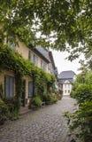 Calle verde con las casas viejas Imagen de archivo