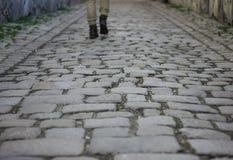 Calle vieja del macadán con las piernas del caminante solo como fondo Imagenes de archivo