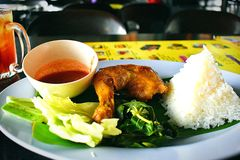 Ayam Penyet Or Chicken Slit. This is called Ayam Penyet. It is a Javanese cuisine. It consists of fried chicken smashed to make it softer and with sambal or stock photography