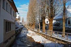 Callejón con nieve al lado del arroyo de Lyssbach en la ciudad de Lyss, pequeña ciudad suiza fotografía de archivo