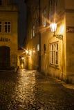 Callejón estrecho misterioso con las linternas en Praga en la noche Foto de archivo