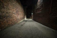Callejón oscuro vacío asustadizo con las paredes de ladrillo imagenes de archivo
