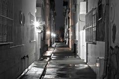 Callejón trasero de la oscuridad en una noche mojada Foto de archivo libre de regalías