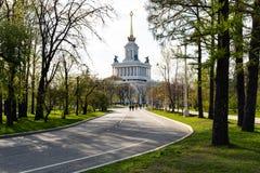Callejón verde en el parque, que lleva a un edificio hermoso alto Primavera imagen de archivo