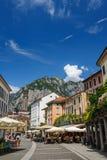 Calles centrales de la ciudad de Lecco, con la gente en café y campanario al aire libre Fotos de archivo