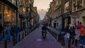 Calles de Amsterdam con caminar de la gente y hombres en bici foto de archivo libre de regalías