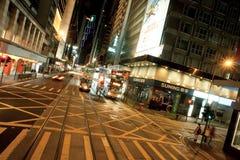 Calles de la ciudad de la noche con la gente que se coloca en cruce con las estructuras urbanas Fotografía de archivo libre de regalías