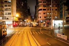 Calles de la noche con los rascacielos y autobús de dos pisos en el camino oscuro Imagen de archivo libre de regalías