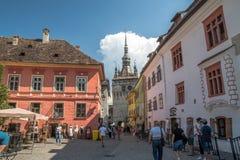 Calles del sighisoara viejo de la ciudad con la torre de reloj foto de archivo