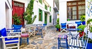 Calles estrechas tradicionales con las barras lindas del café en Grecia Isla de Skopelos, Sporades foto de archivo