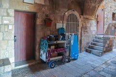 Calles silenciosas de Jerusalén Un carro con los soportes de libros religiosos en el cuarto judío cerca de una pared en la ciudad foto de archivo