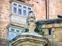 Calles tranquilas de la capital de Malta - La Valeta La estatua del león que sostiene un escudo en la esquina de la calle y del a Imagen de archivo