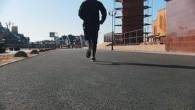 Calles urbanas Un hombre atlético que corre en la calle almacen de video