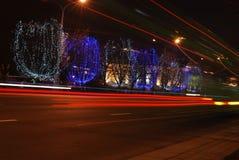 Calles y árboles de la noche con las luces Imágenes de archivo libres de regalías