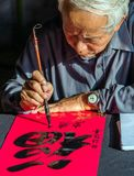 Calligrapher Old Master Is Writing Ancient Letter Words On Red P Royalty Free Stock Photos