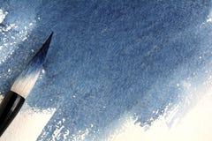 Calligraphic borste som befläckas med blå målarfärg på ett ark av vattenfärgpapper med indigoblå fläck royaltyfri bild