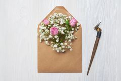 Calligraphic feather an envelope with flowers and a letter, greeting card for Valentines Day with place for your text. Flat lay, top view photo mock up Stock Images