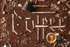 Calligraphic inscription coffee. Calligraphic inscription gothic letters coffee over ground black coffee scattered on white marble with roasted and unroasted stock photography