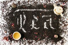Calligraphic inscription tea. Calligraphic inscription gothic letters tea over dry black ceylon and green tea scattered on white marble with rose buds, ceramik royalty free stock images