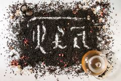 Calligraphic inscription tea. Calligraphic inscription gothic letters tea over dry black ceylon and green tea scattered on white marble with rose buds, stainer stock image