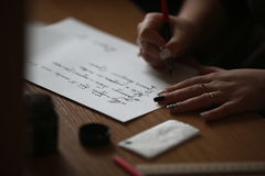 Calligraphic letter. The girl writes a letter with pen and ink stock photo