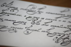 Calligraphic letter. Sheet of paper with a poem written calligraphic letters royalty free stock photos