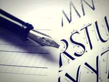 Calligraphic letters and fountain pen. Close up of a calligraphy pen and paper stock images