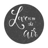 Calligraphic sign -Love is in the air in a circle with grunge effect. Calligraphic sign -Love is in the air in a circle Royalty Free Stock Photo