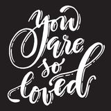 Calligraphic you are so loved phrase. Handwritten  white font on black background Royalty Free Stock Photos