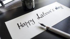 Calligraphie de travail heureuse de jour du ` s et carte postale lattering Vue gauche avec le stylo de calligraph Photographie stock libre de droits
