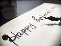 Calligraphie de travail heureuse de jour du ` s et carte postale lattering Vue gauche avec le stylo de calligraph Images libres de droits
