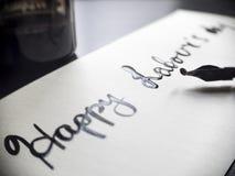 Calligraphie de travail heureuse de jour du ` s et carte postale lattering Vue gauche avec le stylo de calligraph Photo libre de droits