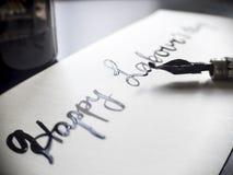 Calligraphie de travail heureuse de jour du ` s et carte postale lattering Vue gauche avec le stylo de calligraph Image libre de droits