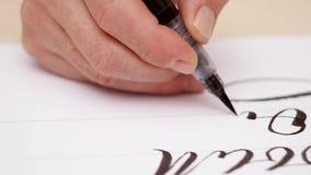 Calligraphist που επισύρει την προσοχή στο άσπρο κενό Στενό πλάνο Μπροστινή όψη Επανδρώνει το χέρι γράφοντας στο άσπρο κενό με τη φιλμ μικρού μήκους