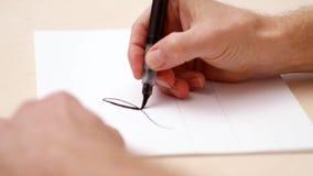 Calligraphist die op witte spatie schrijven Dicht schot Zachte nadruk Het kalligrafische van letters voorzien Bemant hand schrijv stock videobeelden