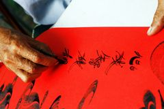 Calligraphy Artist of Vietnam. Calligraphy artist in Saigon or Ho Chi Minh City, Vietnam writing on red paper Royalty Free Stock Photo
