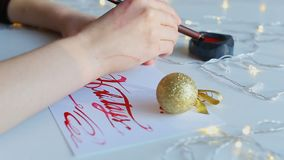 Calligraphy in decorated place on holidays. Drawing word holidays with broad nib pen and red ink. Twinkling yellow garland and fir tree toy. Concept of stock footage