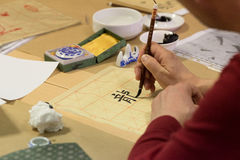 Calligraphy exercise. Student making strokes with brush on calligraphy exercise in workshop Stock Images