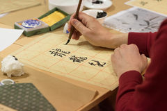Calligraphy exercise. Student making strokes with brush on calligraphy exercise in workshop Royalty Free Stock Photo