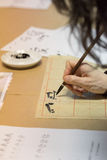 Calligraphy exercise. Student making strokes with brush on calligraphy exercise in workshop Royalty Free Stock Image