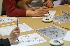 Calligraphy exercise. Student making strokes with brush on calligraphy exercise in workshop Stock Photos